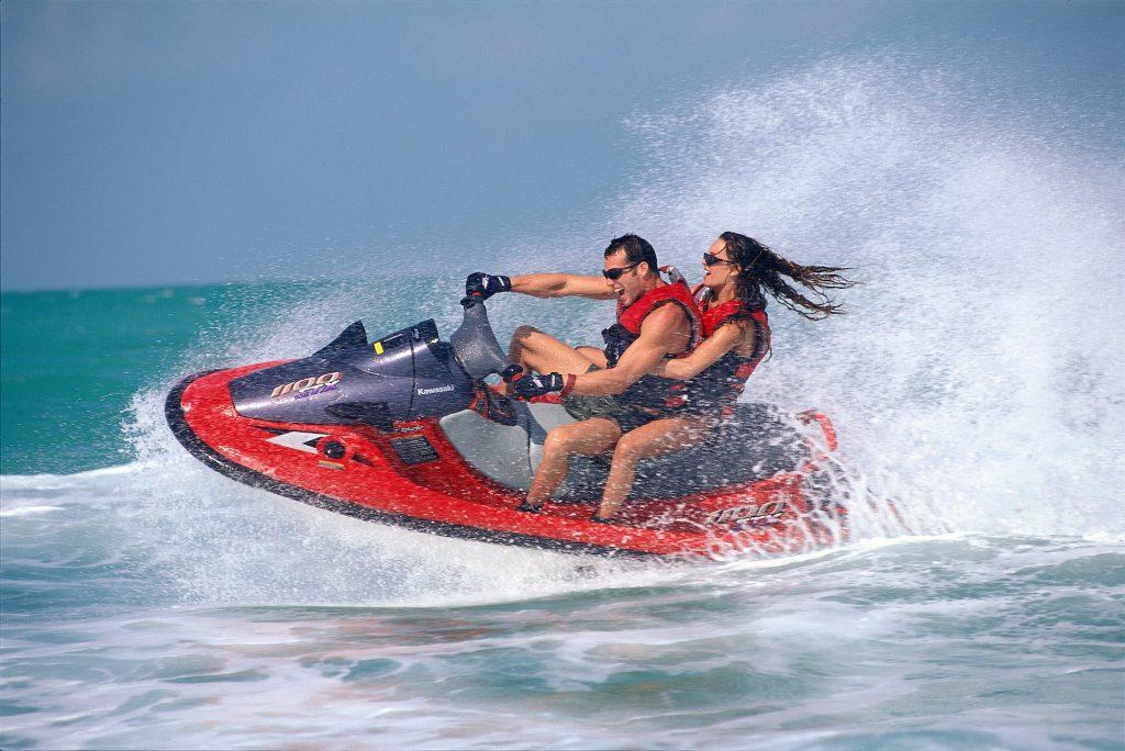 A young couple rides a Kawasaki Jet Ski personal watercraft near Islamorada in the Florida Keys