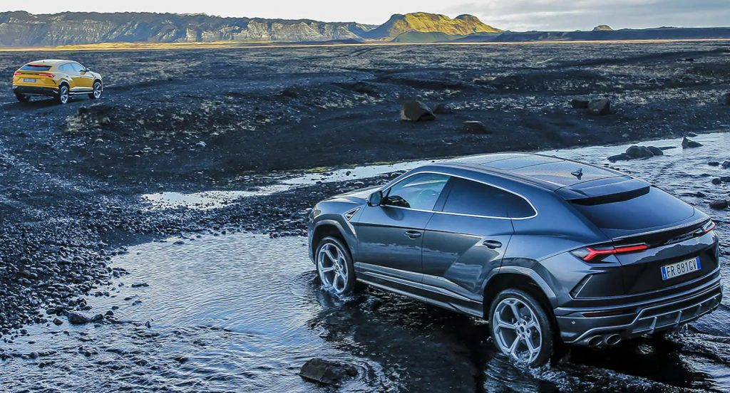 Two Lamborghini Urus SUV models (one yellow, one black) are out exploring nature.