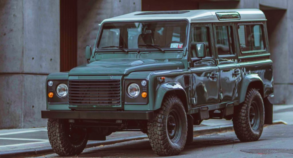 A custom-built Land Rover Defender 110 by Brooklyn Coachworks is parked. The vehicle was restored and modified by Brooklyn Coachworks.