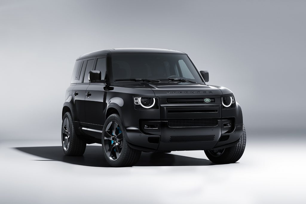 Land Rover Defender V8 Bond Edition in all black. Photo shot in a white studio. Vehicle is facing the camera with the front wheels slightly turned to the viewer's right, revealing a hint of the blue brake calipers.