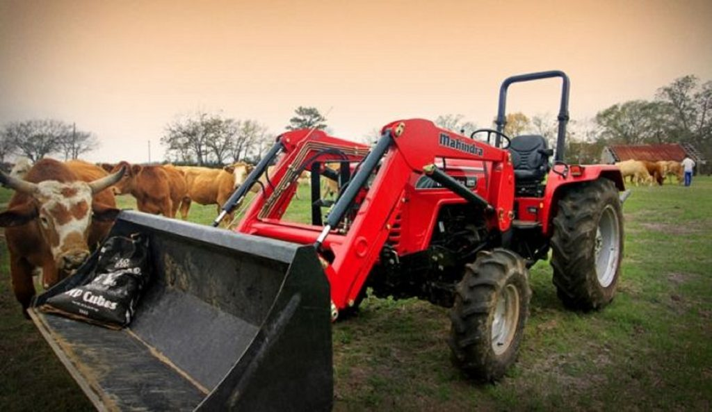 A red Mahindra 4540 4WD compact utility tractor amongst some cows