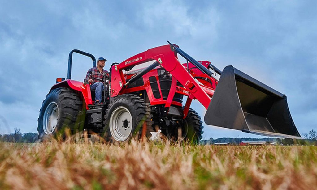 A farmer operates a red Mahindra 5100 Series utility tractor in a field