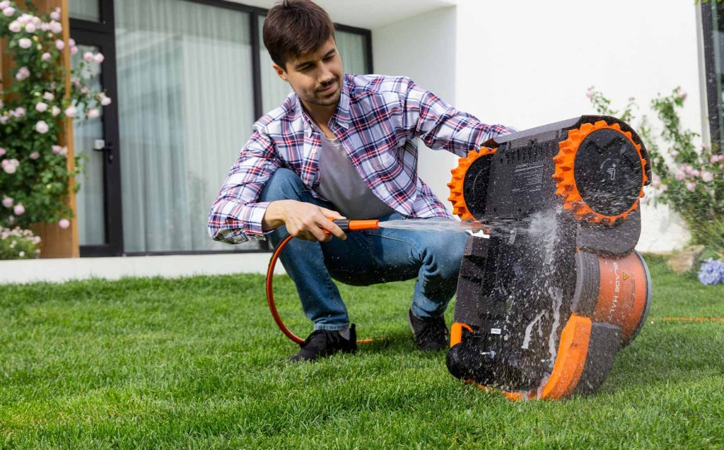 A man washes a Segway Navimow with a hose in the middle of his lawn