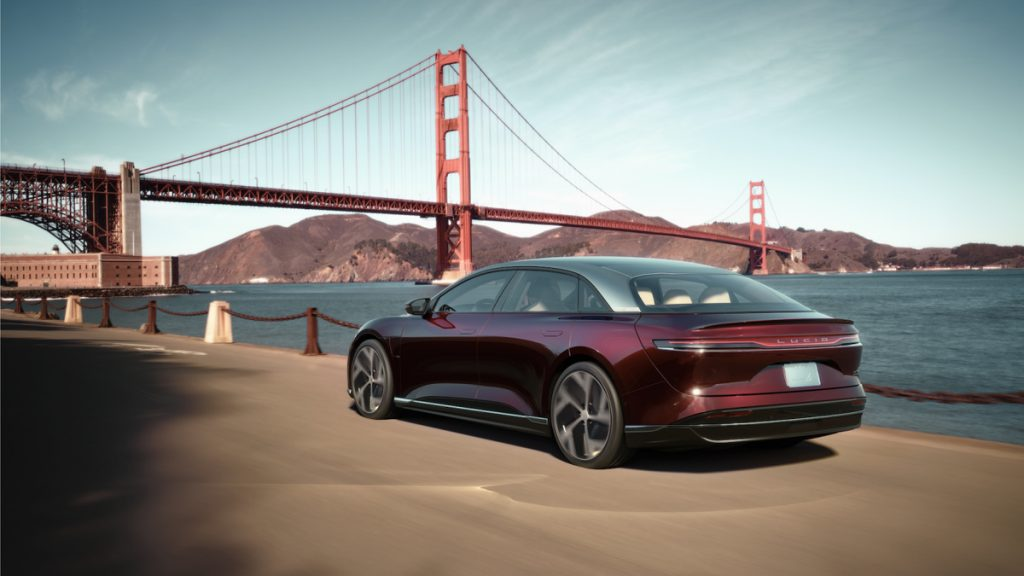 Maroon Lucid Air parked in front of the Golden Gate Bridge