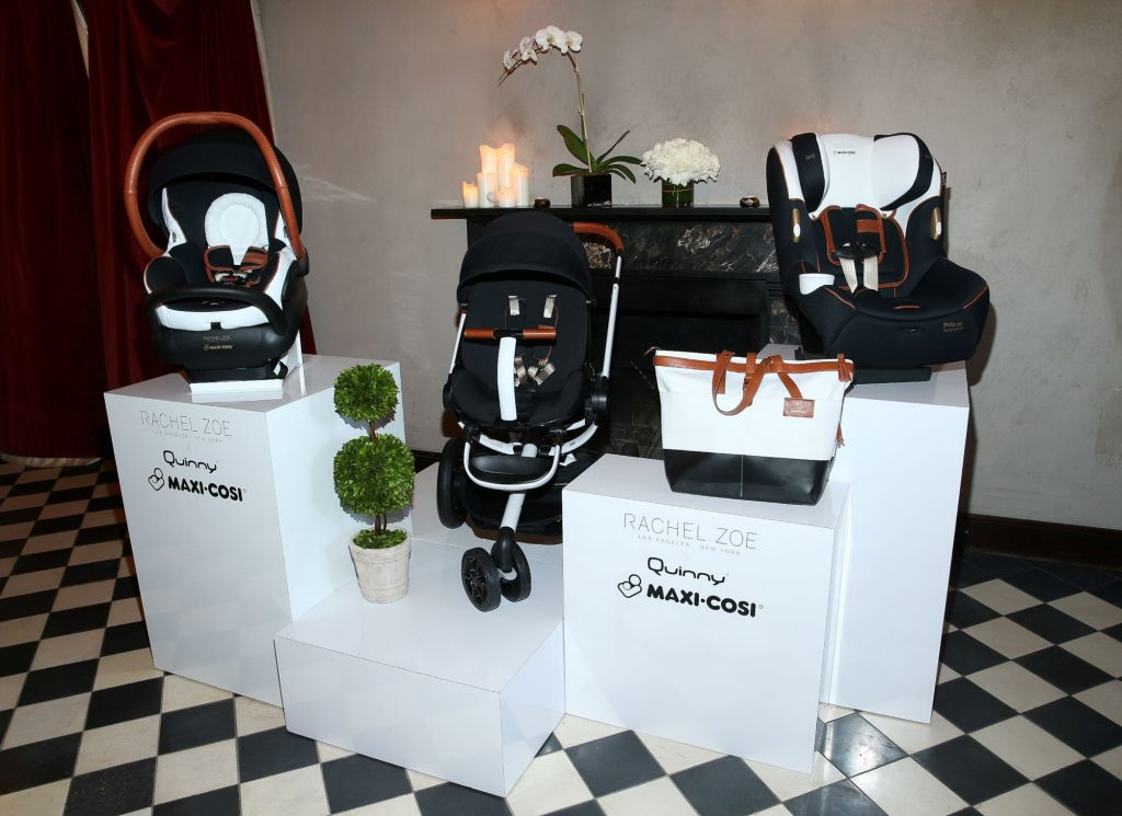 Maxi-Cosi car seats and bags displayed on a white platform on a black and white checkered floor.