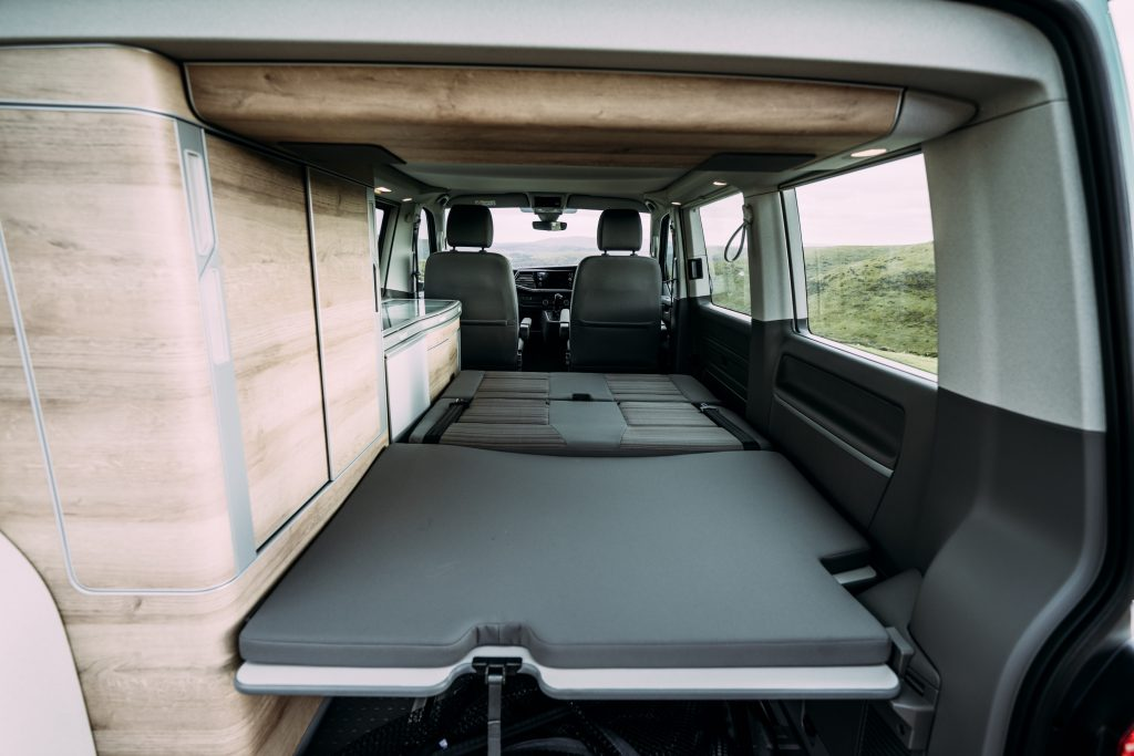 Volkswagen California camper van interior with the bed laid out.