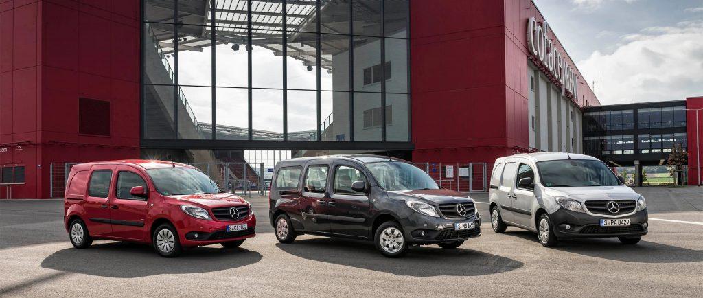 A trio of Mercedes-Benz Citan vans parked outside of a large building