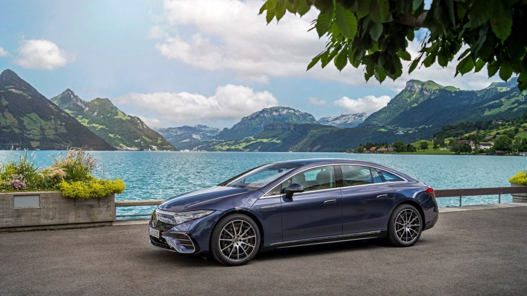 A blue Mercedes-Benz EQS sitting on a concrete area in front of a large body of water with mountains in the background.