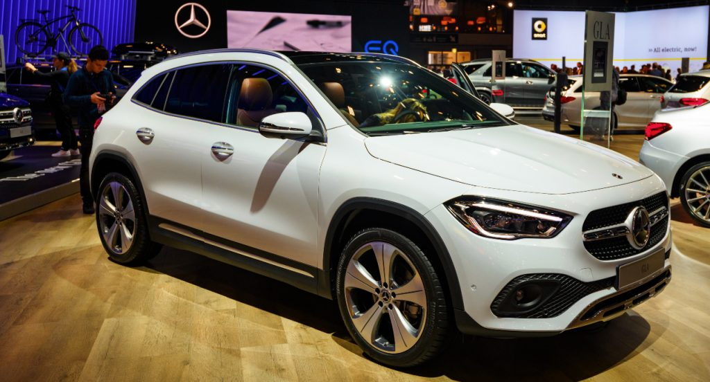 A white Mercedes-Benz GLA luxury SUV is displayed in a showroom.