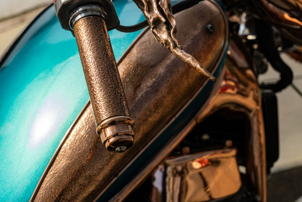 The close-up view of the fuel tank and right handlebar on Mike Prete's turquoise-and-copper custom 1998 Suzuki Intruder