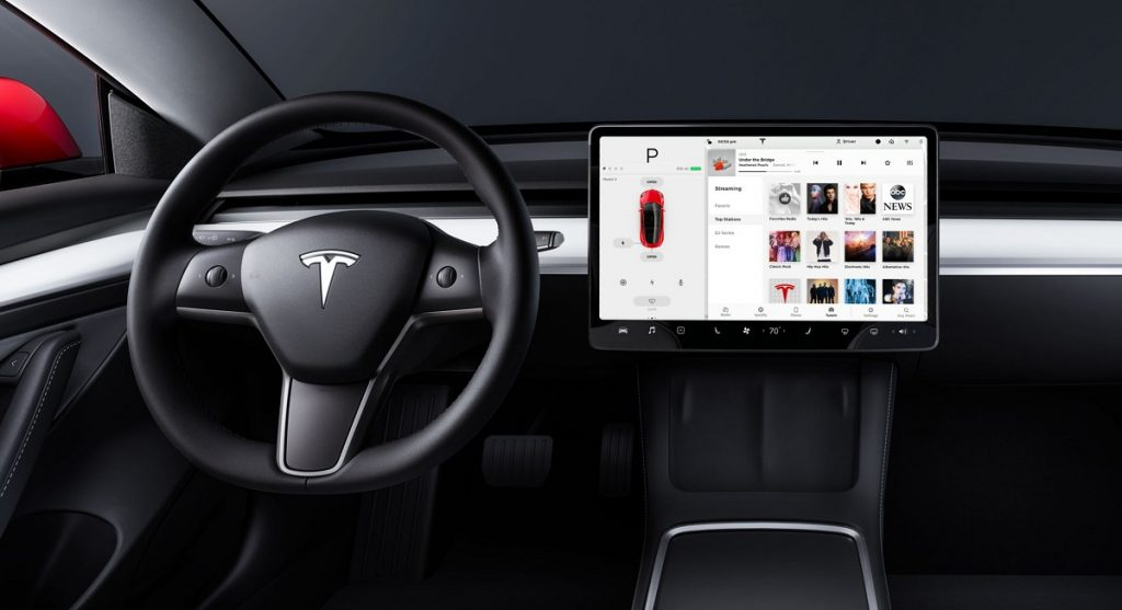 The steering wheel and screen of the inside of a Tesla Model 3.