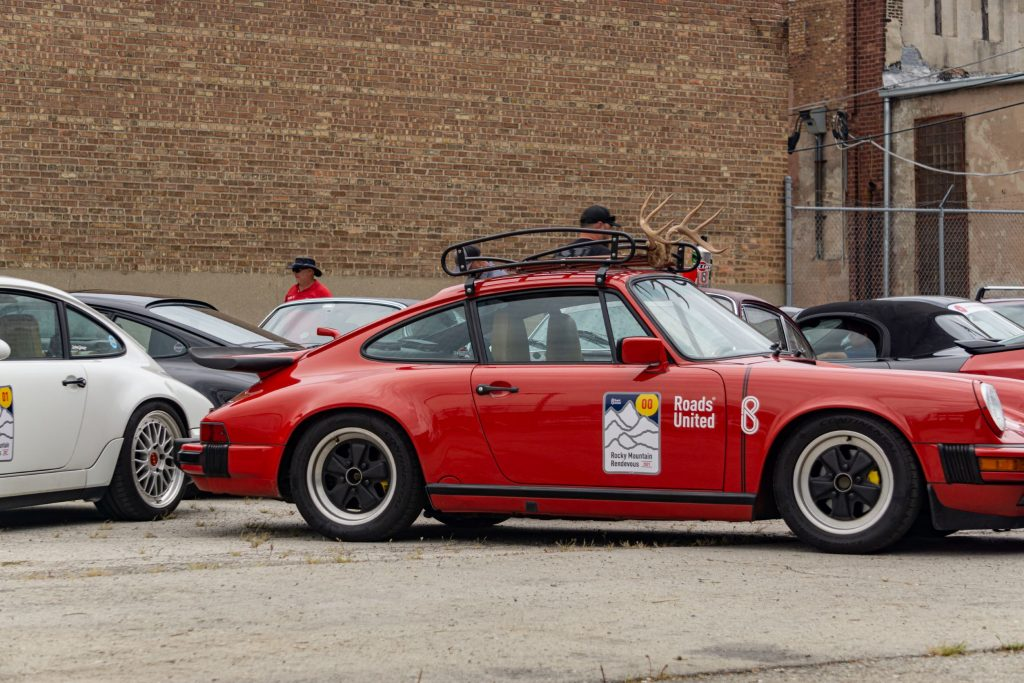 The side view of a modified red 1987 Porsche 911 Carrera 3.2 in a parking lot amongst other Porsche cars