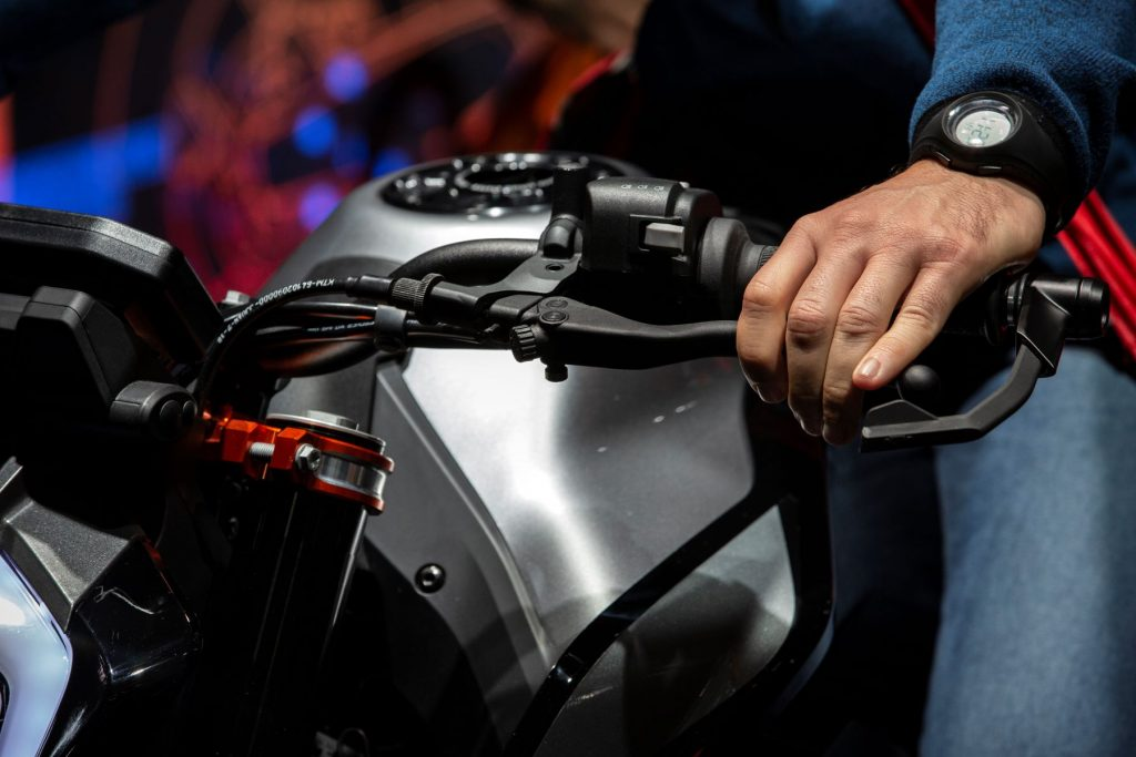 A driver with their hands on a KTM motorcycle's brakes