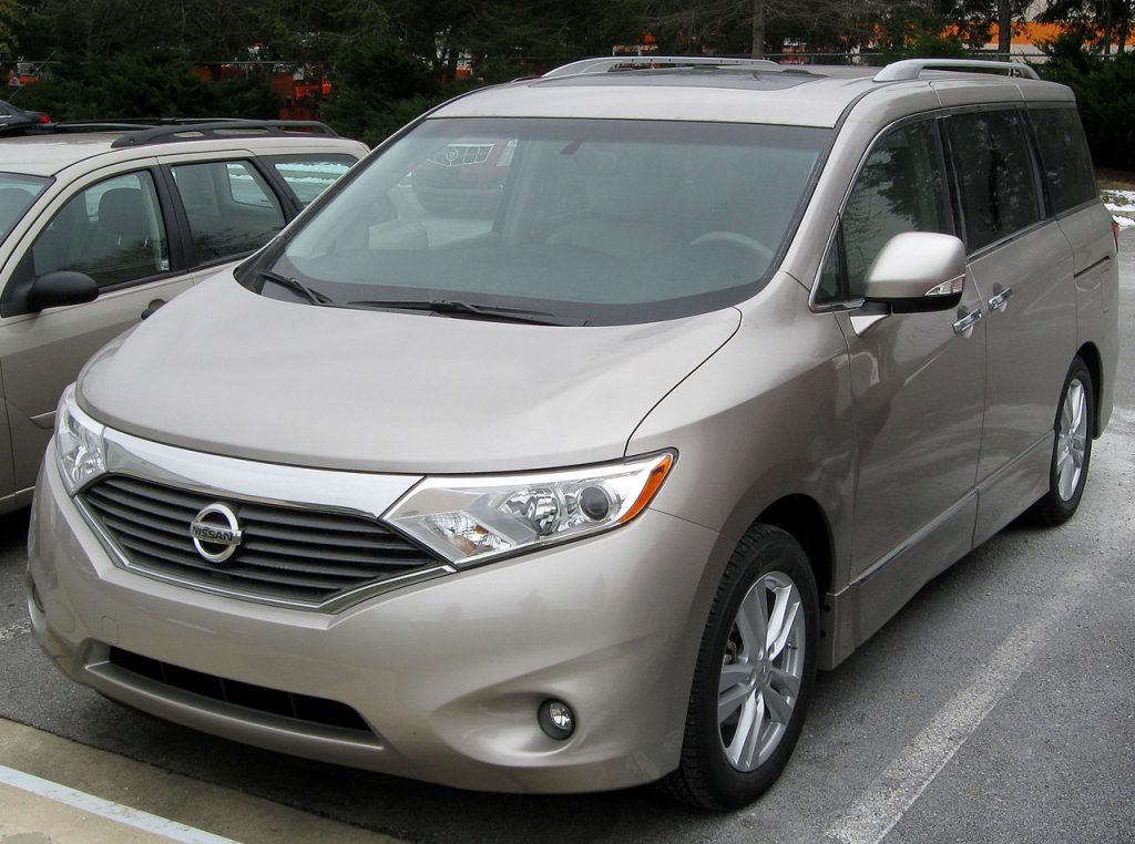 a gold 2011 nissan quest parked in a parking lot during the day