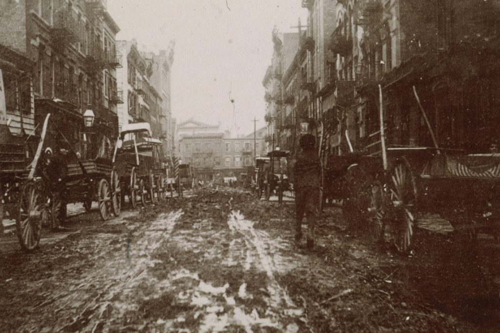 circa 1899: Carriages sit in the mud on either side of Willet Street between Stanton and Houston Street prior to the construction of 'Bone Alley Park,' New York City.