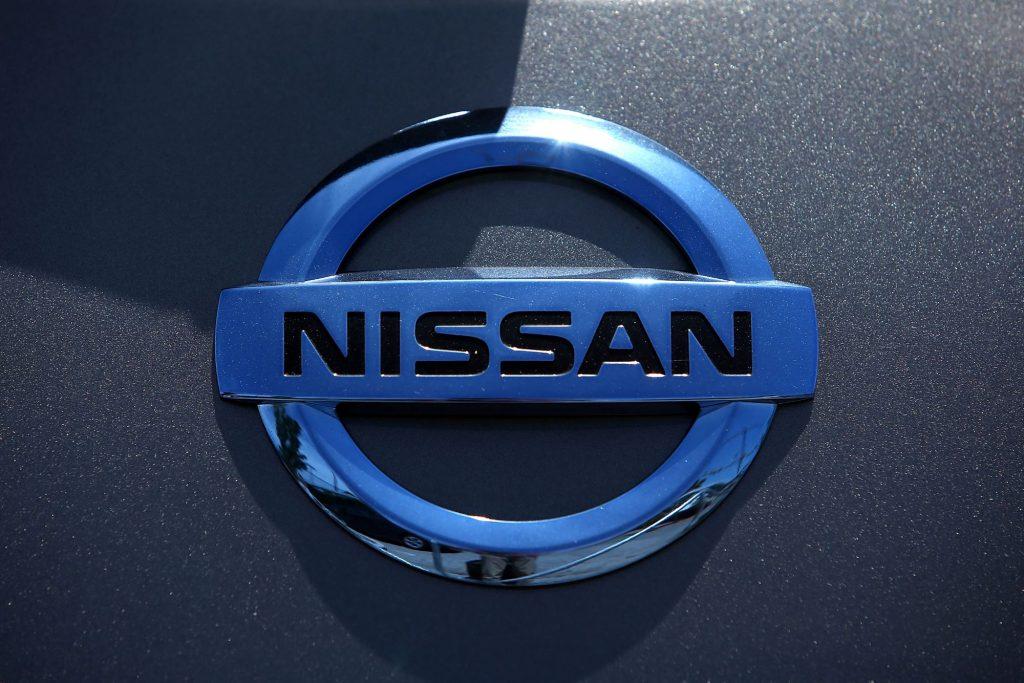 Chrome Nissan logo on a grey car.