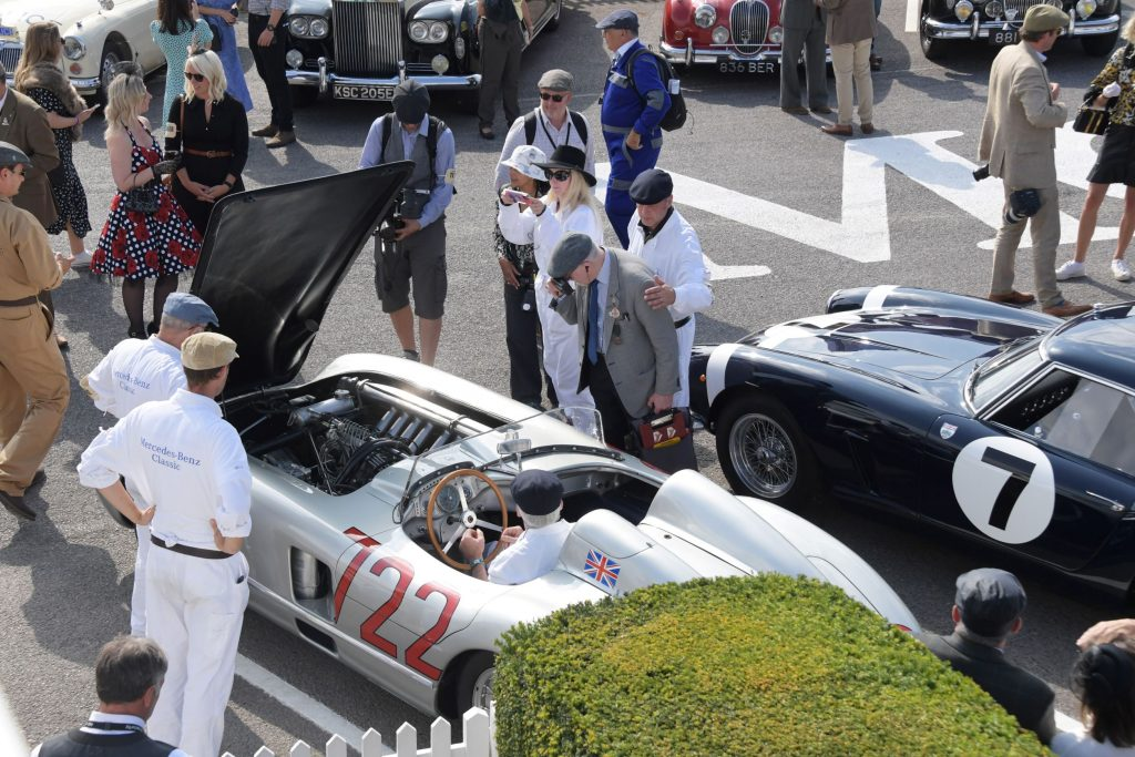 Onlookers in vintage clothing look at classic cars at the 2021 Goodwood Revival, including Sir Stirling Moss's silver No. 722 1955 Mercedes-Benz 300 SLR