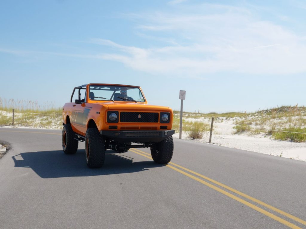 Orange and black 1979 International Harvester Scout driving by sand dunes