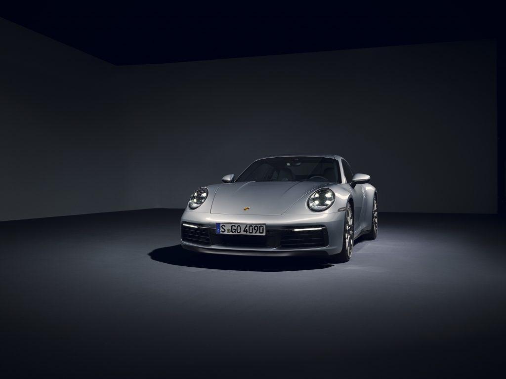 A silver Porsche 911 Carrera in a photo studio