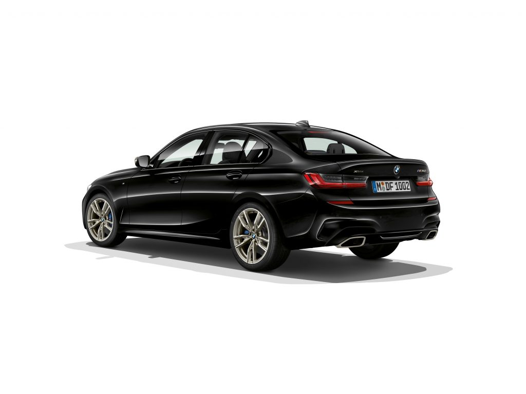 A black BMW M340i Xdrive shot against a white background from the rear 3/4 angle