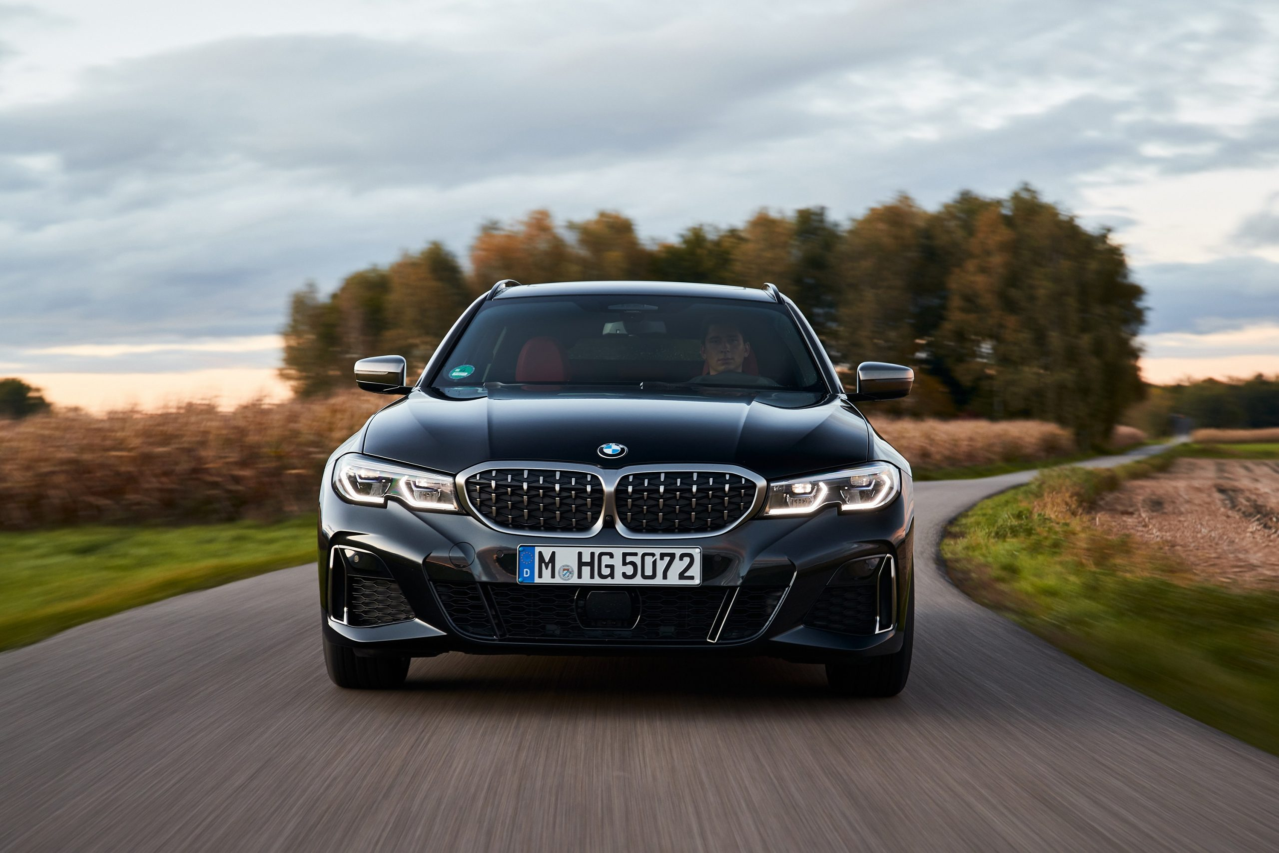 The current BMW 3 series blasts down an autumn road