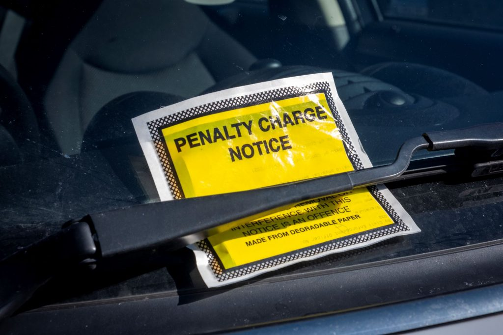 A bright yellow parking violation ticket on a vehicle under the windshield wiper.