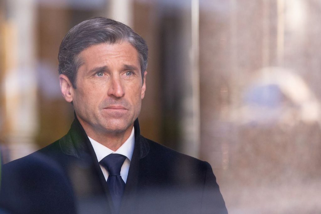 Patrick Dempsey looking through a window with a few reflections form the outside dressed in a black suit.