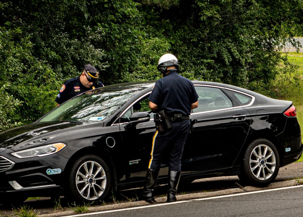 Two police officers pulling over a for unsafe or illegal activity black car.