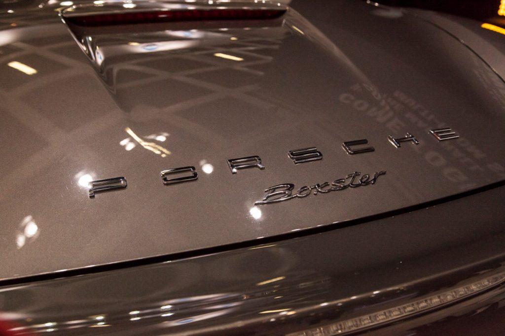 Porsche Boxster logo on a coffee colored car.