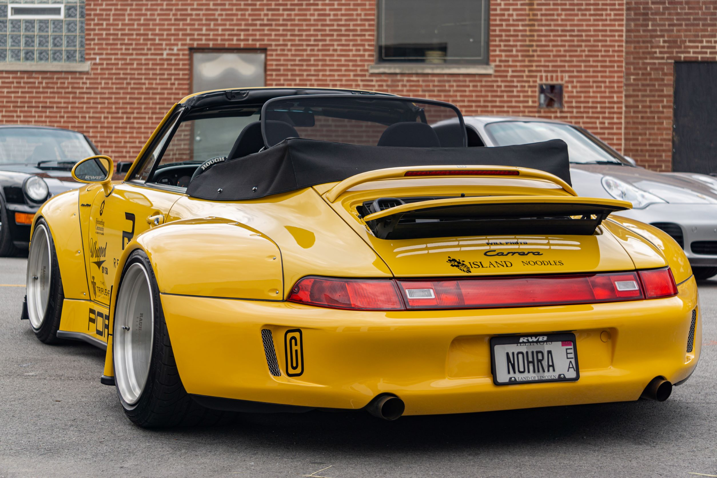 The rear view of the yellow-and-black RWB Porsche 993 911 Cabriolet 'Nohra'