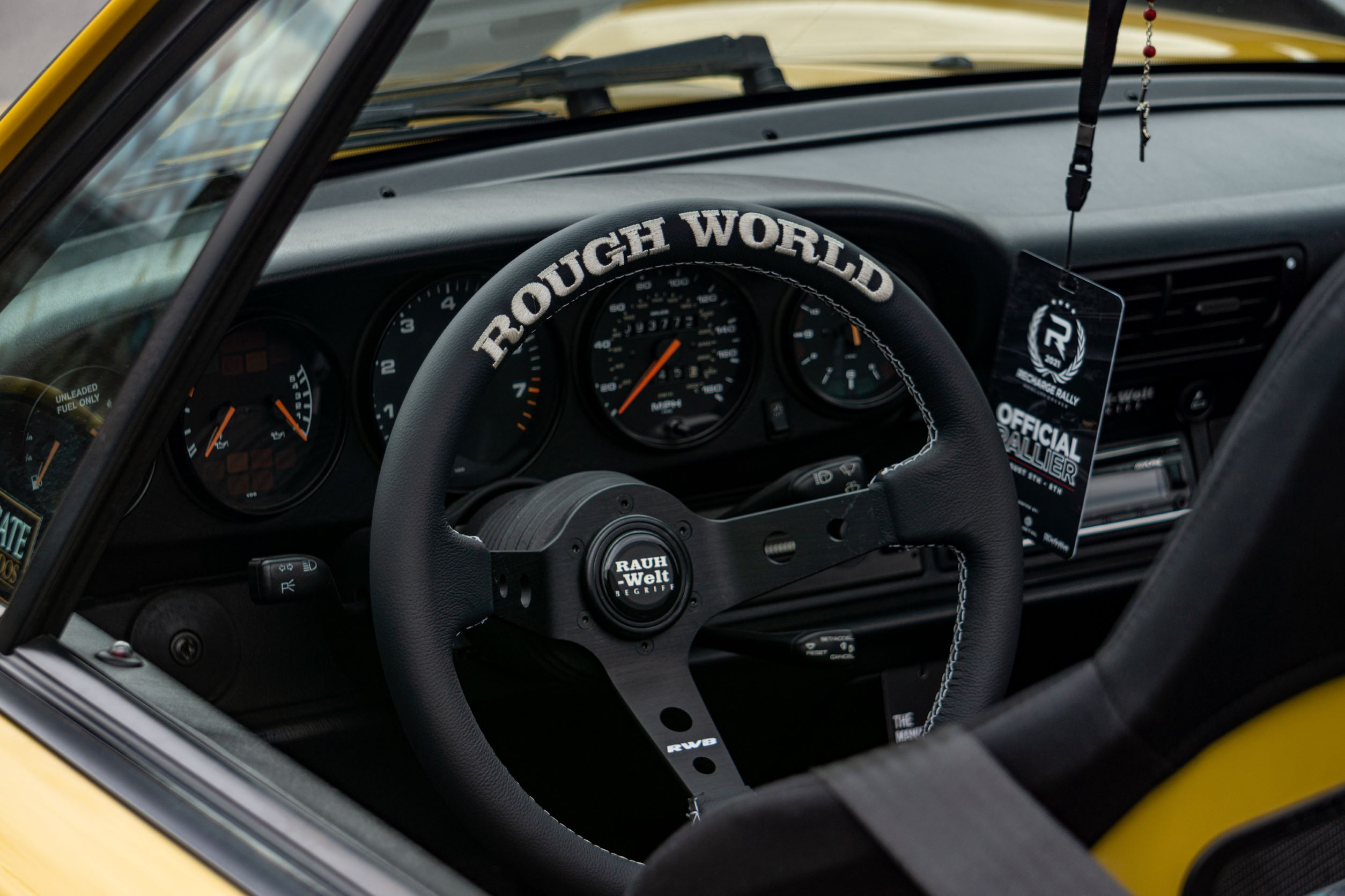 The black steering wheel, gauges, and seat of the yellow-and-black RWB Porsche 993 911 Cabriolet 'Nohra'