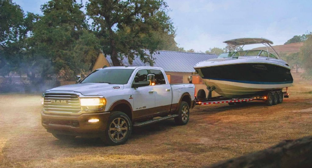 A white Ram 2500 heavy duty truck is towing a white boat.