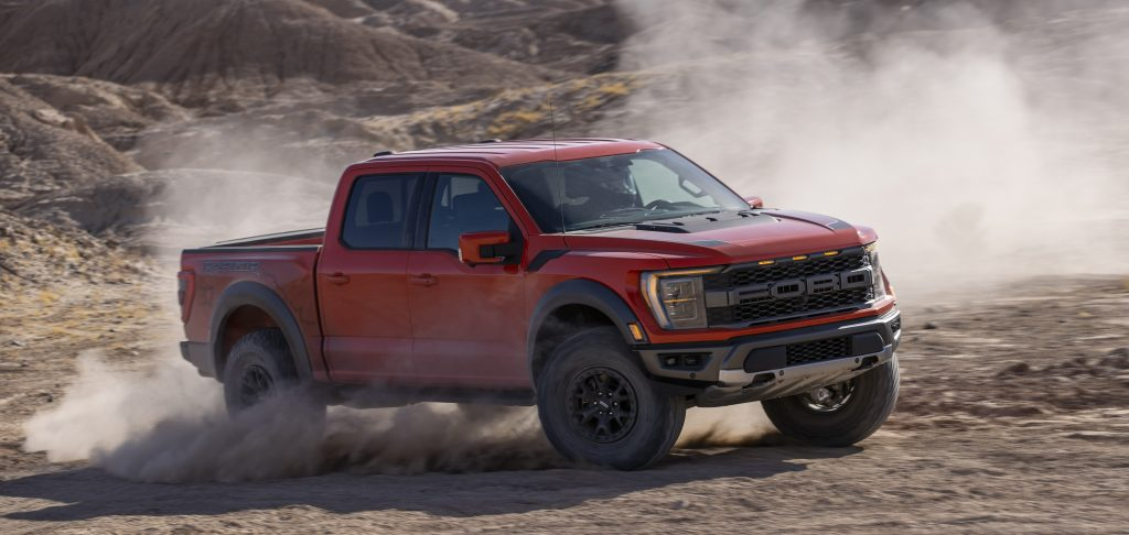 Red 2021 Ford F-150 Raptor driving on mountainous terrain