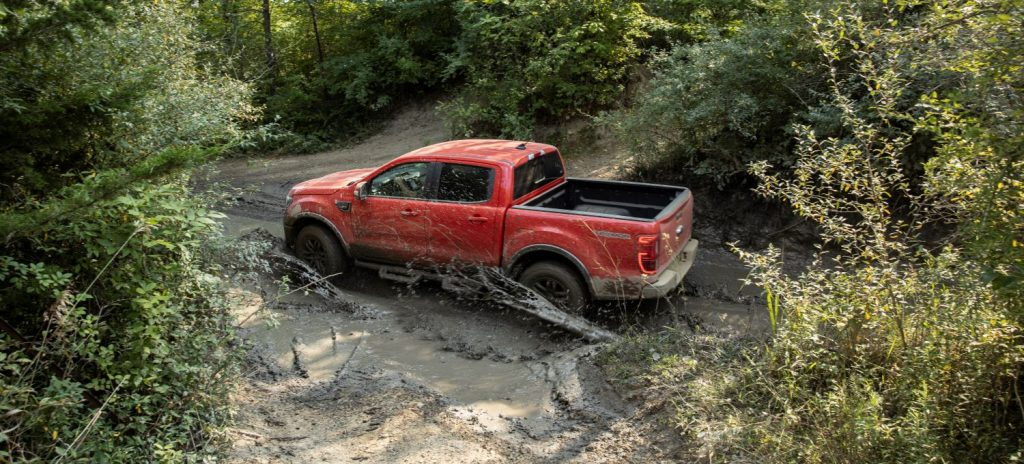Red 2021 Ford Ranger driving on a muddy road