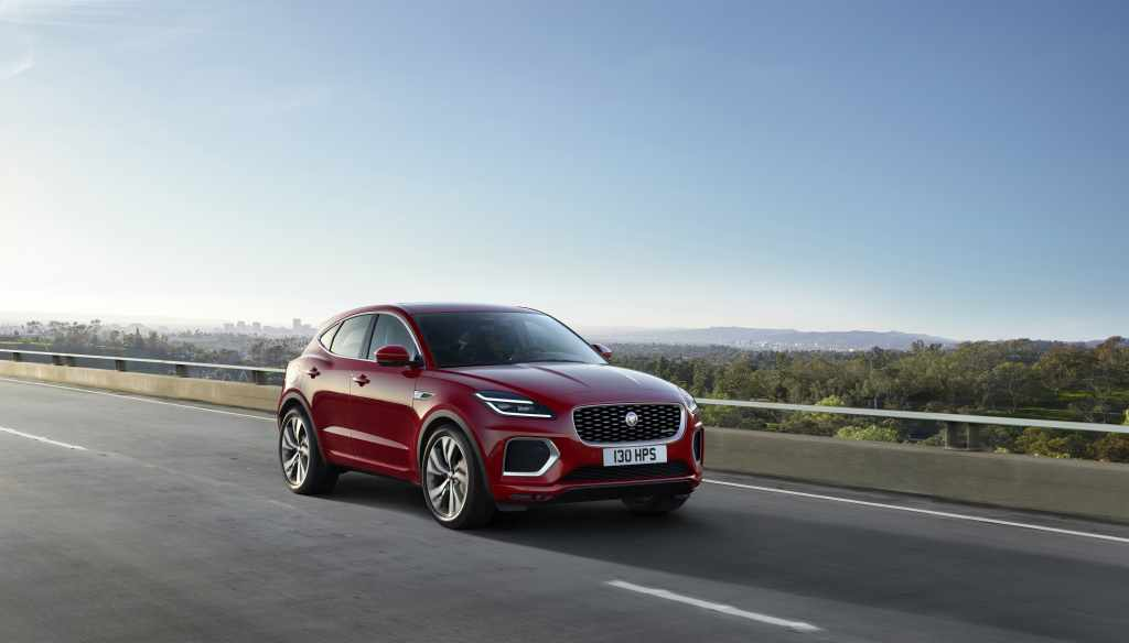 Red 2021 Jaguar E-PACE driving by a forested area