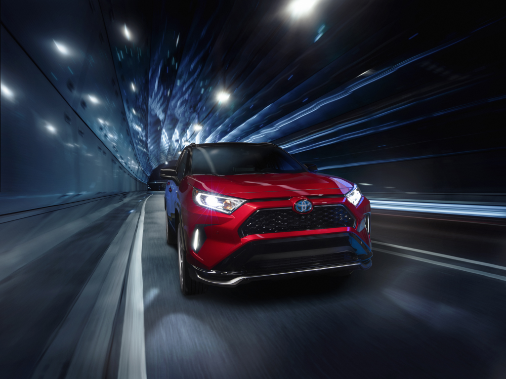Red 2021 Toyota RAV4 Prime driving through a tunnel