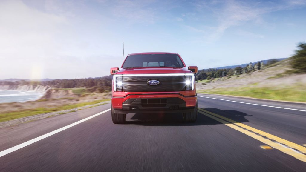Red 2022 Ford F-150 Lightning driving on a coastal road