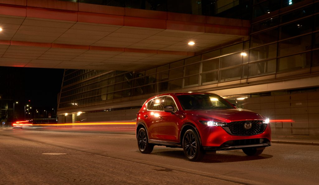Red 2022 Mazda CX-5 driving by a large building at night