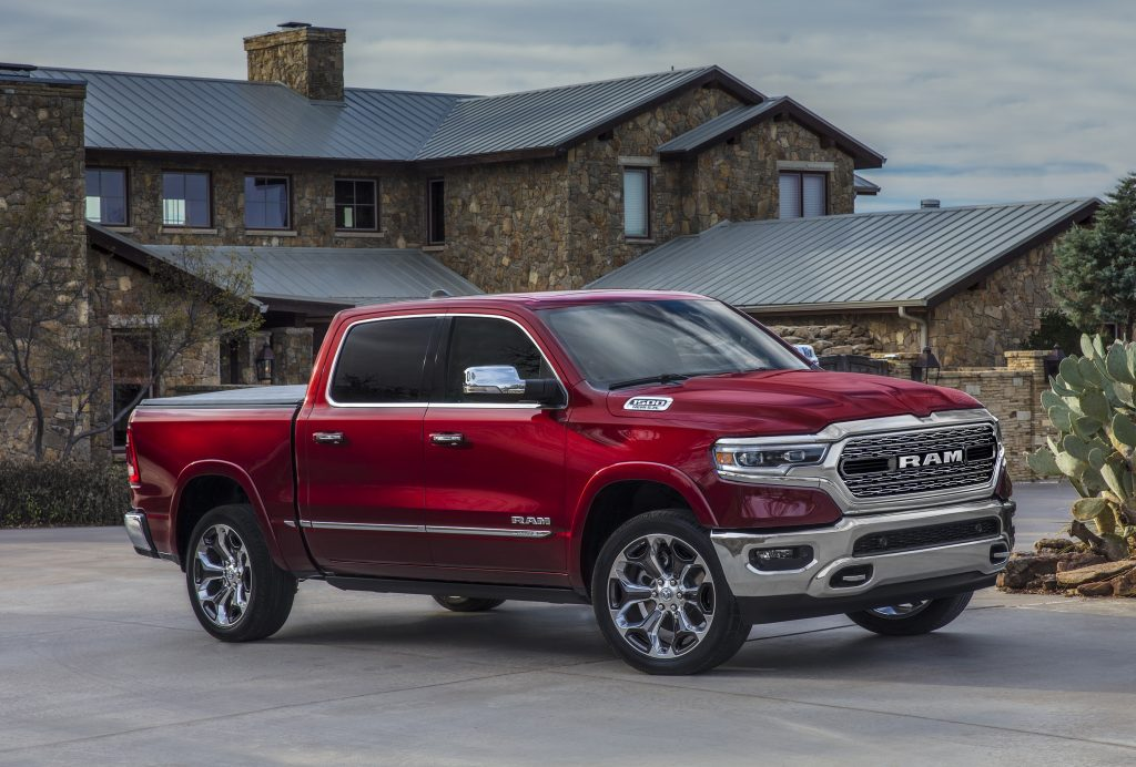 Red 2022 Ram 1500 parked in front of a large house