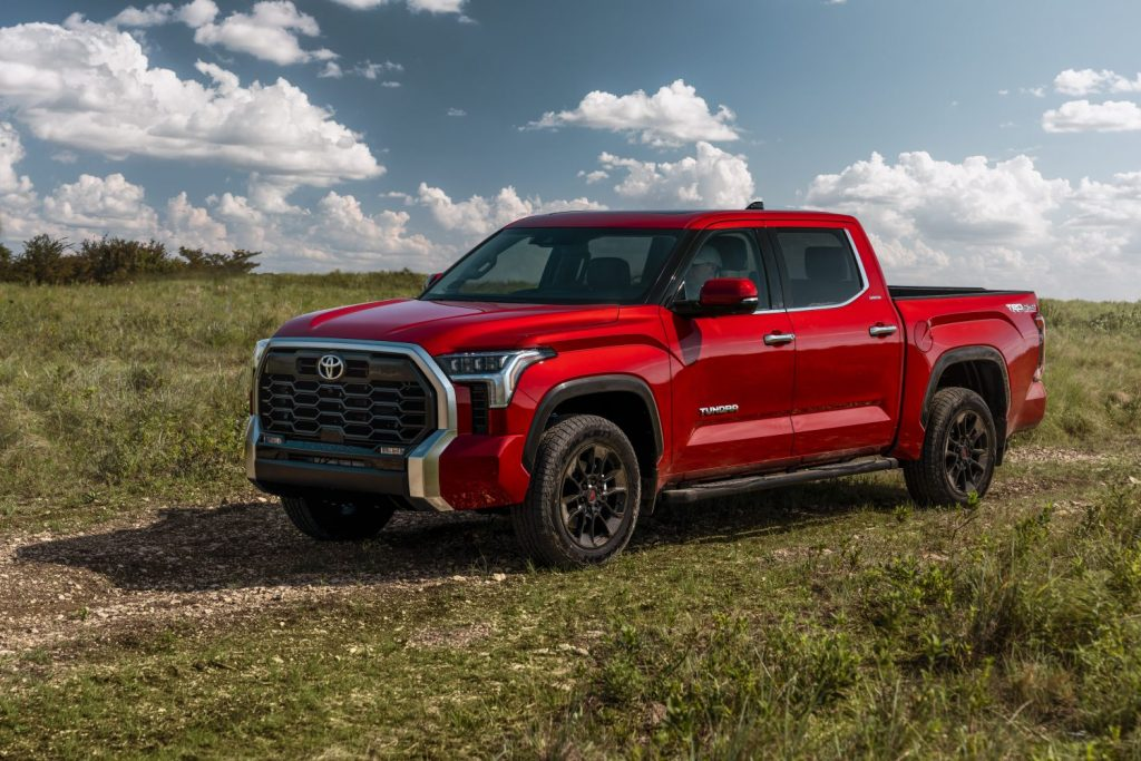Red 2022 Toyota Tundra parked in a grassy field