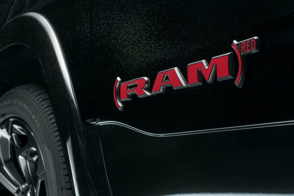Red badge on black 2022 Ram 1500 Limited (RAM) RED Edition driving down a street