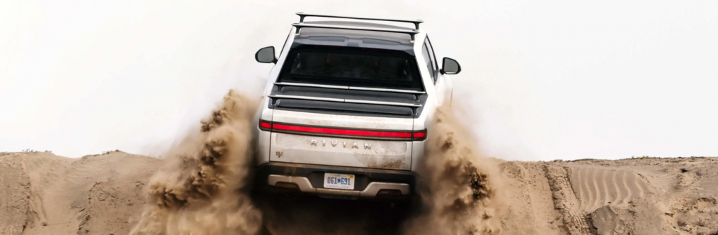 The Rivian R1T electric truck model driving on sand dunes