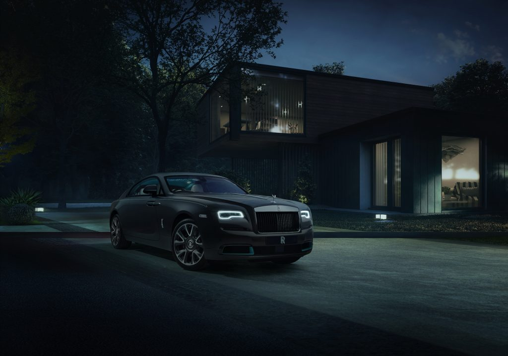 A dark-colored Rolls-Royce Wraith Kryptos parked in front of a modern house at night