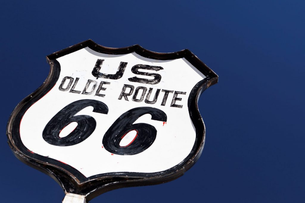 Route 66 sign in against a blue sky.