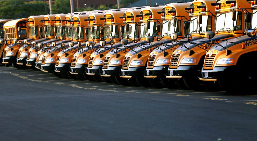 Row of school buses in a parking lot David L. Ryan The Boston Globe via Getty Images