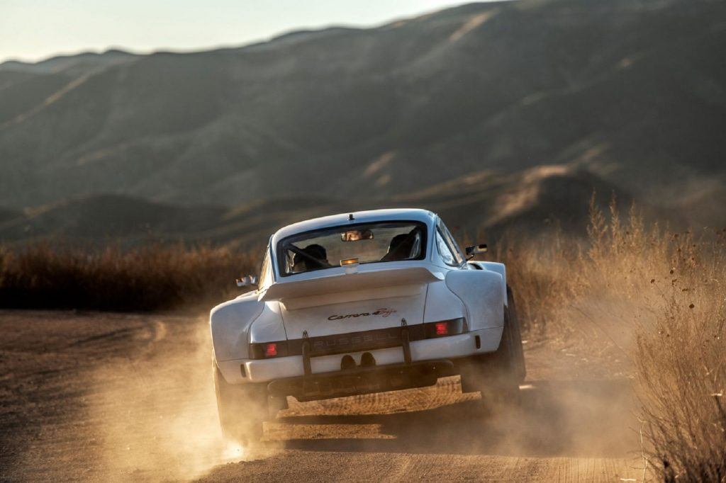The rear view of a white Russell Built Fabrications Baja 911 sliding in the desert
