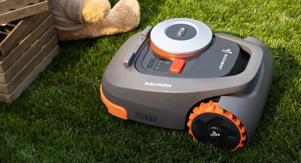 A segway navimow sits in a lawn area next to a wooden box and teddy bear