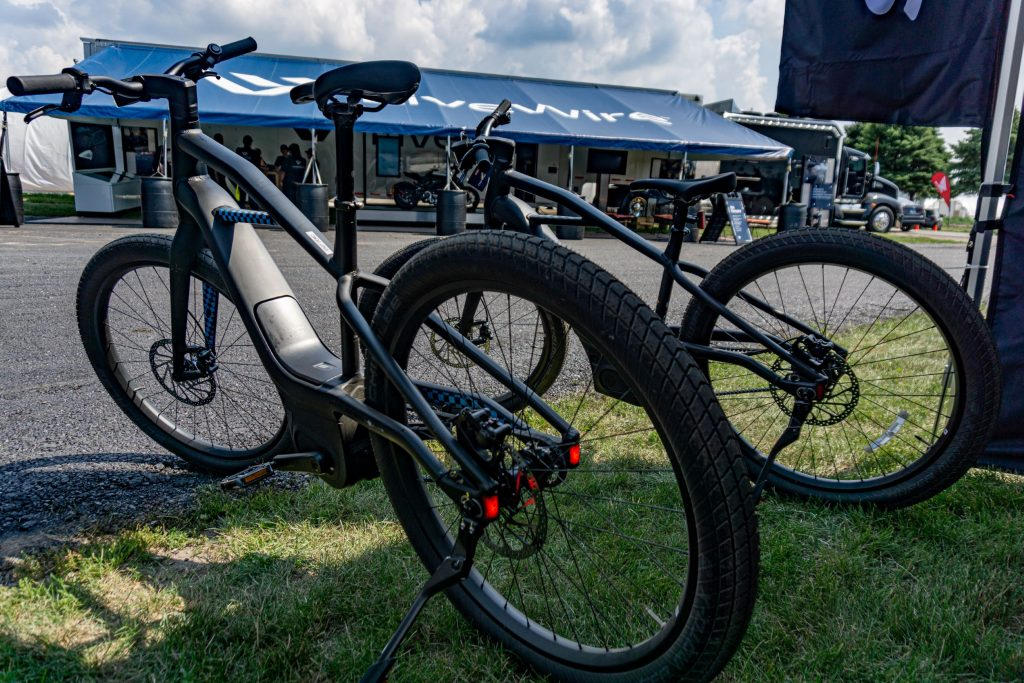 The rear 3/4 view of two black Serial 1 MOSH/CTY ebikes under a tent