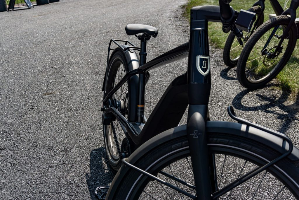 The front 3/4 view of a black Serial 1 RUSH/CTY Speed ebike on an asphalt path