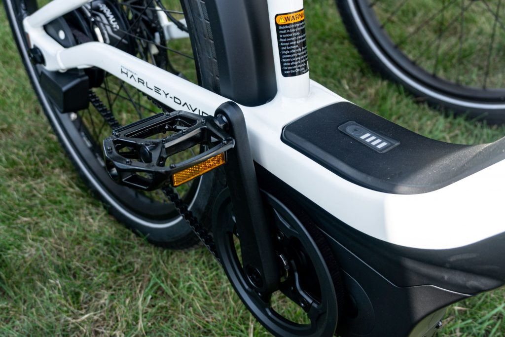 A close-up view of a black-and-white Serial 1 RUSH/CTY Step-Thru ebike's pedals, battery, and motor